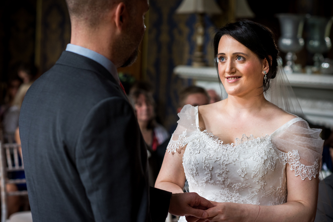 Image of the bride gazing at her groom during the wedding ceremony at Soughton Hall.