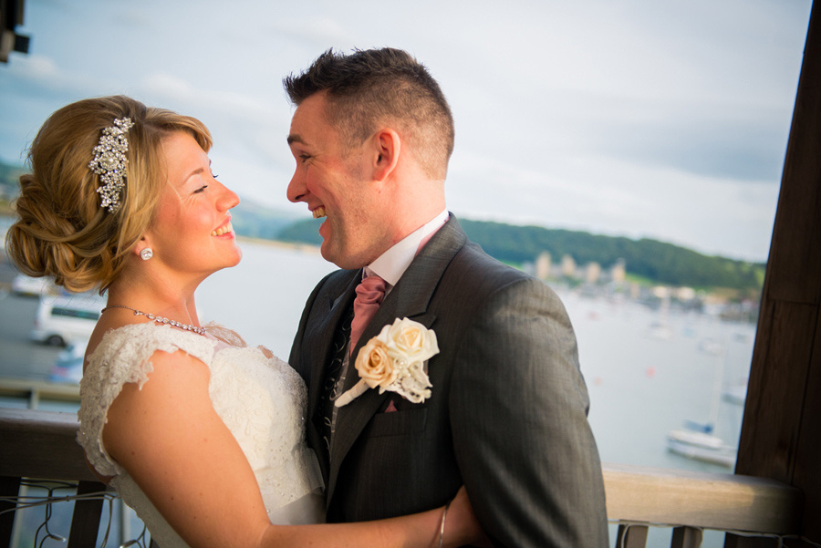 bride and groom laughing on the balcony at the Deganwy Quay. Wedding Photographer: Celynnen Photography