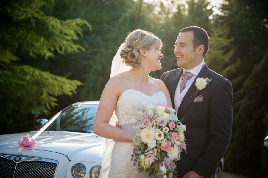 Bride and Groom Smiling Together by Wedding Car by North Wales Wedding Photographer Celynnen Photography