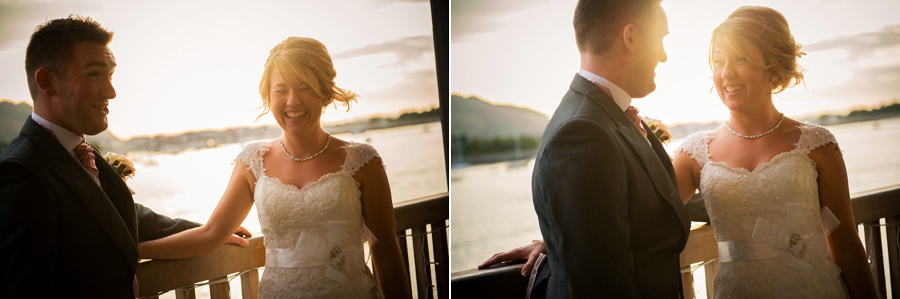 The bride and groom laughing as the sun sets at the Deganwy Quay. Wedding Photographer: Celynnen Photography