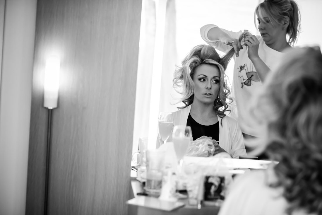 Black and white image of the bride getting her hair done in preparation for her wedding day at Portmeirion.