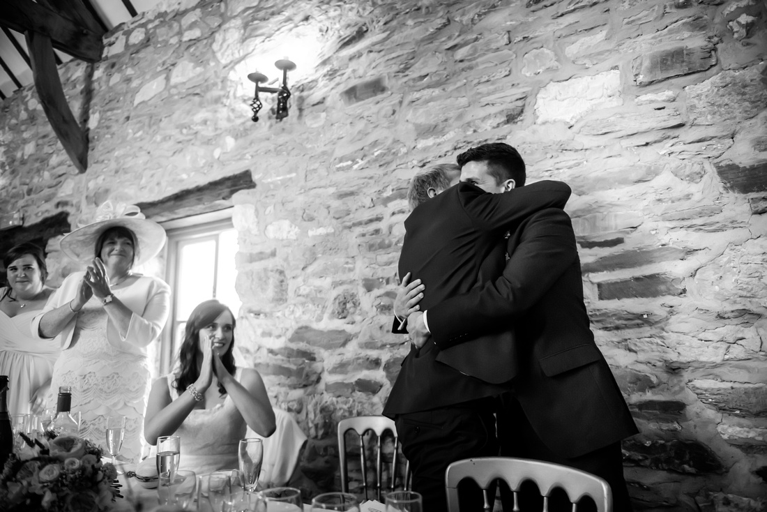Black and white image of the groom hugging the best man after his speech at his wedding at Plas Isaf.