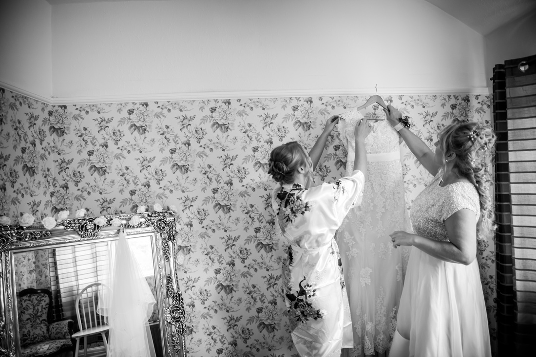 Black and White image of mother helping the bride in preparation for the day at The Kinmel.
