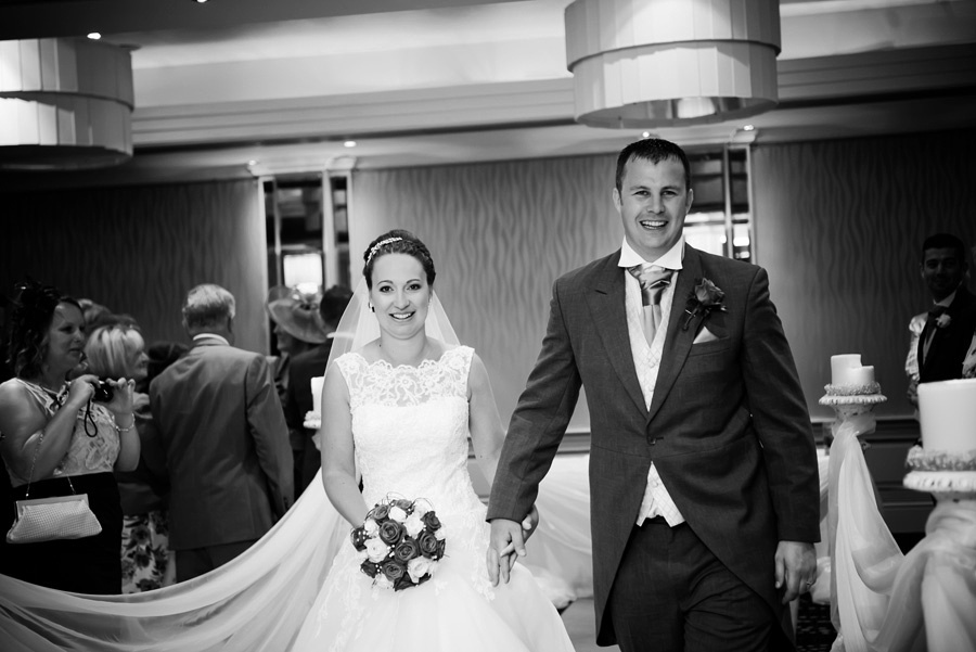 Black and white image of the bride and groom leaving the wedding ceremony as a married couple at Grosvenor Pulford