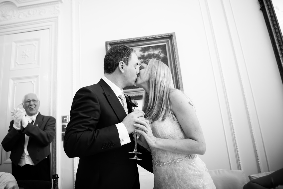 Black and white image of the bride and groom kissing during the speeches at their wedding at Taplow House, Buckinghamshire.