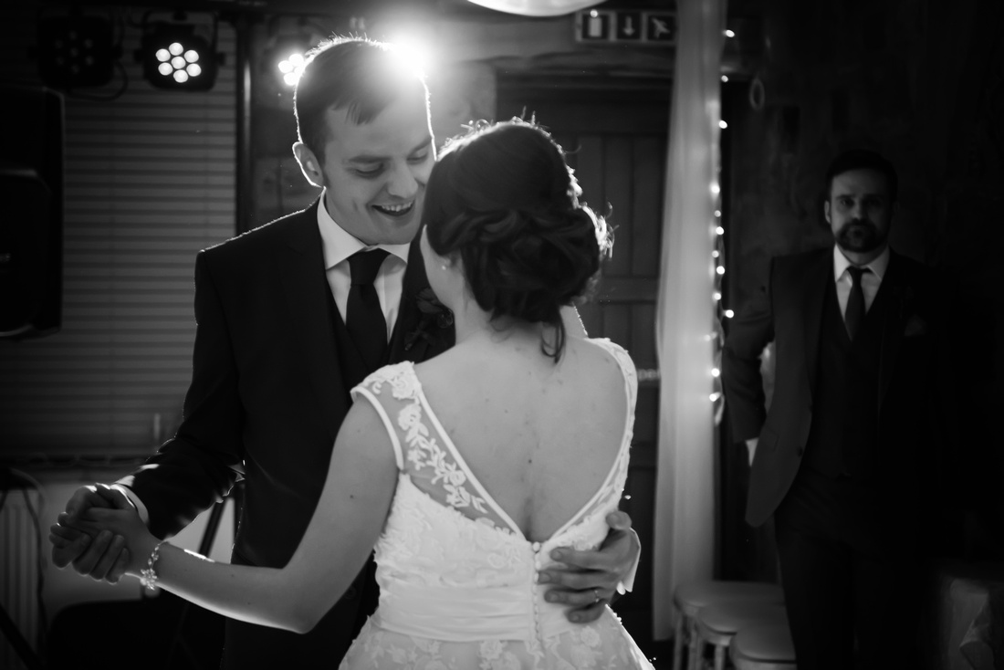 Black and white image of the bride and groom enjoying their first dance at Beeston Manor.