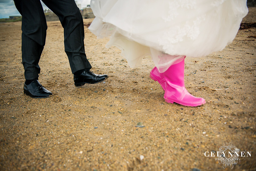 Bride and groom showing off their shoes on the beach in Caernarfon