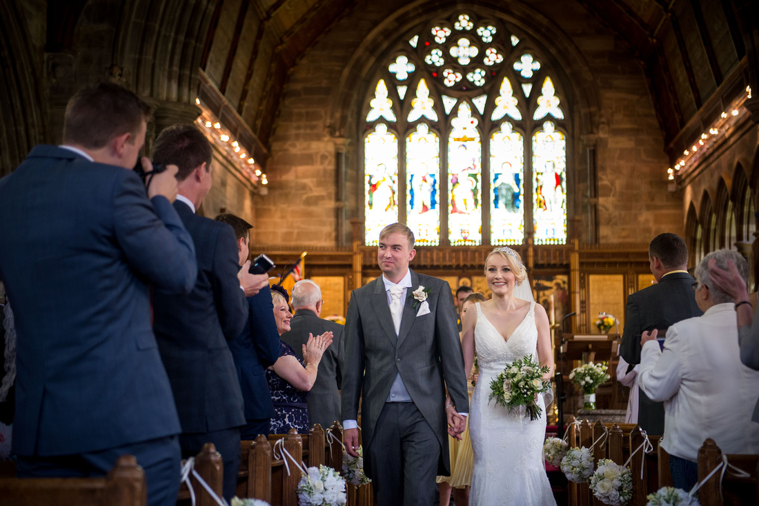 Image of the bride and groom leaving the church as a married couple. Location is Halkyn.