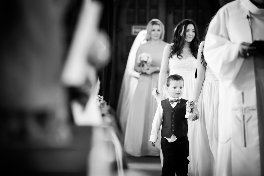Black and white image of the bridal party walking down the aisle at a wedding in Buckinghamshire.