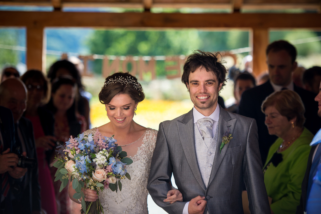 Image of the bride walking down the aisle with her brother at a wedding at Tower Hill Barns.