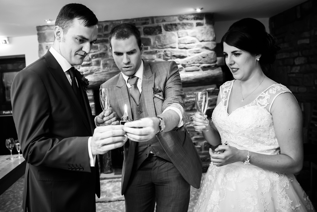 Black and white image of bride and groom being entertained by a magician at their wedding at Beeston Manor.