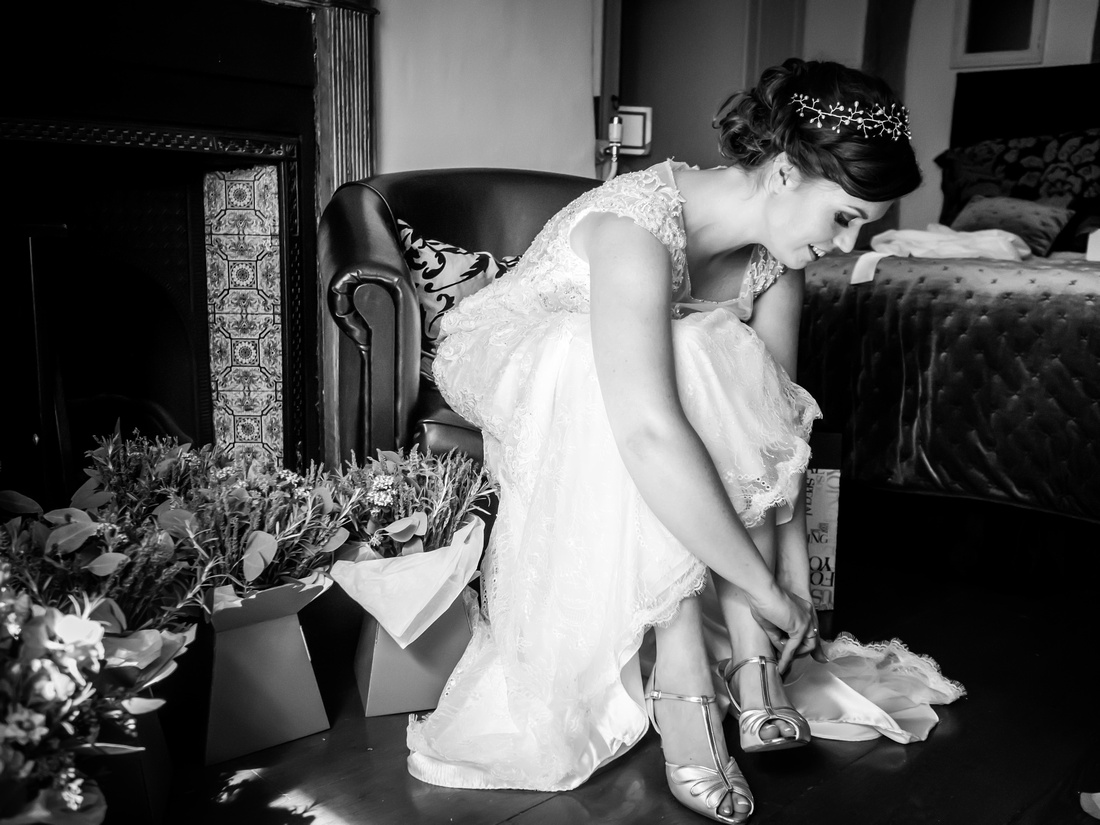 Black and white image of bride putting on her shoes for her wedding day at Tower Hill Barns.