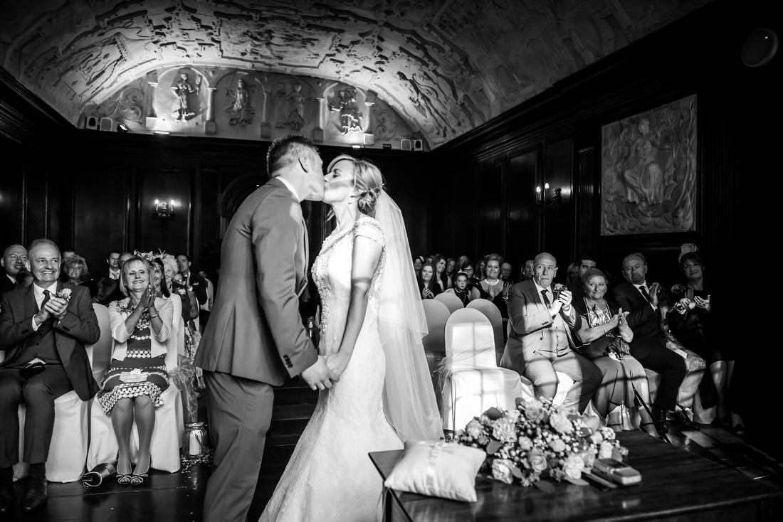 Black and white image of bride and groom sharing their first kiss as a married couple. Wedding in Portmeirion.
