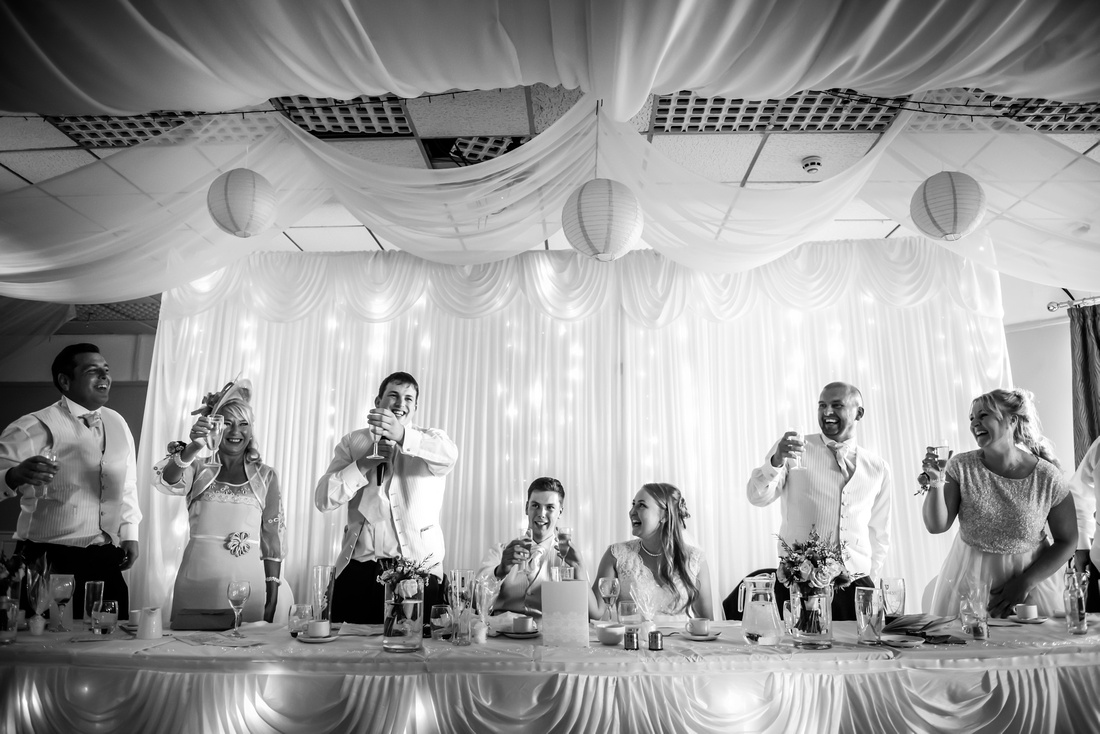 Black and white image of everyone making a toast to the bride and groom, from wedding at The Kinmel.