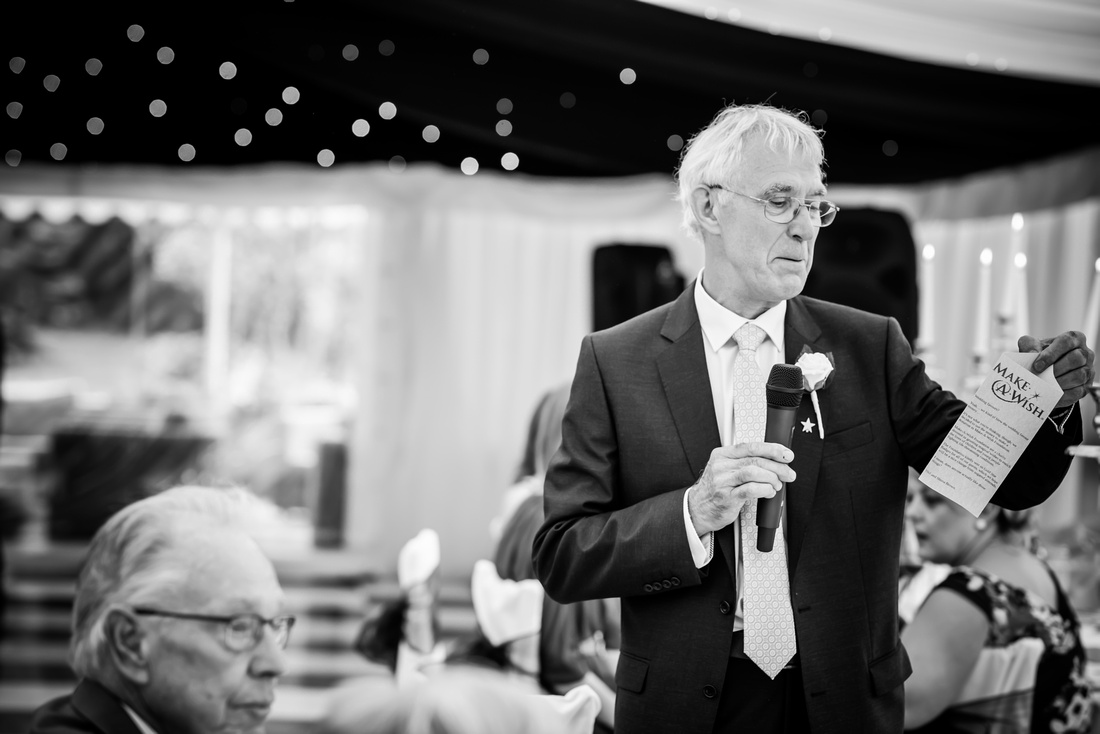 Black and white of a guest doing a speech at a wedding at Soughton Hall.