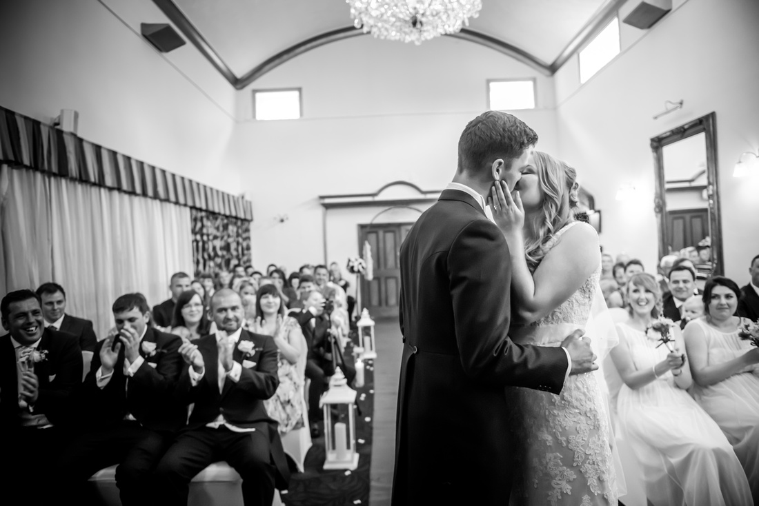 Black and white image of the bride and groom's first kiss as a married couple. Wedding at The Kinmel near Abergele.