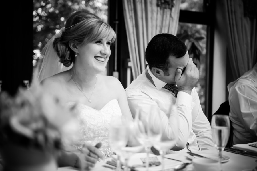 Bride and Groom Laughing at Speeches by North Wales Wedding Photographer Celynnen Photography