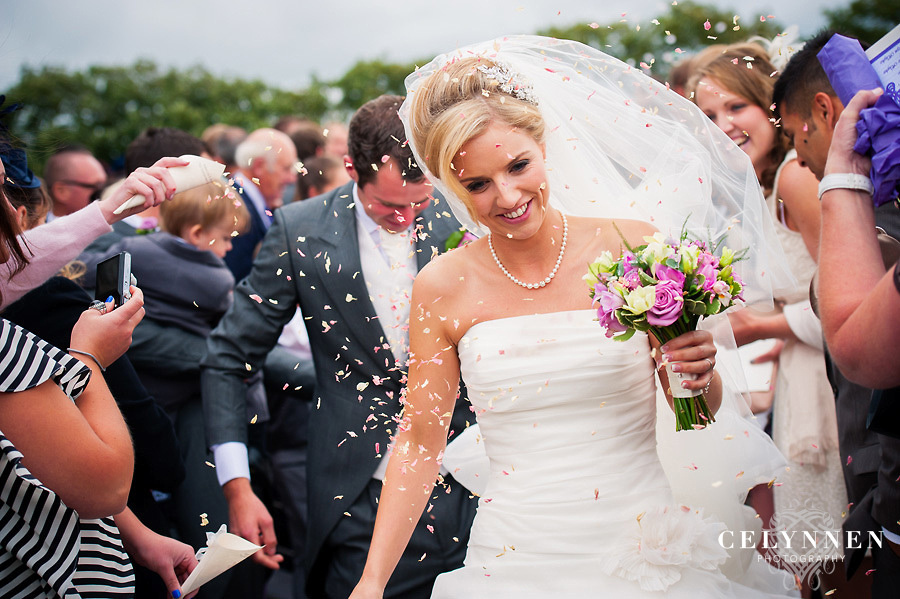 Bride and groom getting showered with confetti at their wedding in Caernarfon