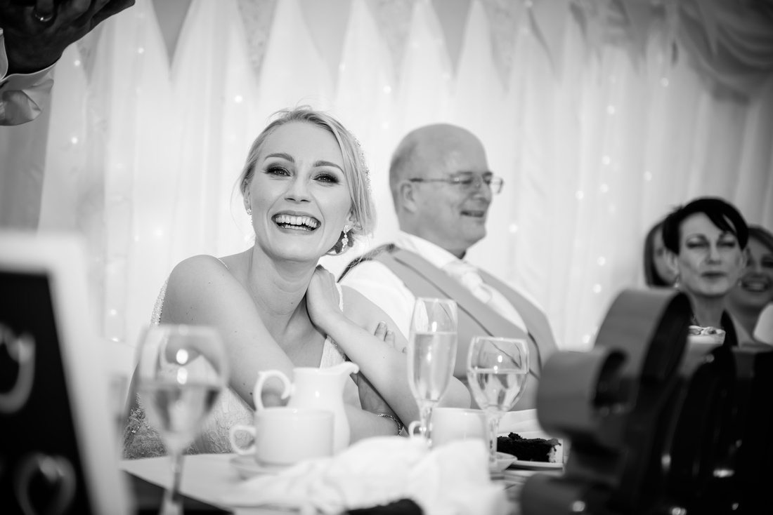 Black and white image of the bride enjoying the speeches at her wedding at Pentre Mawr.