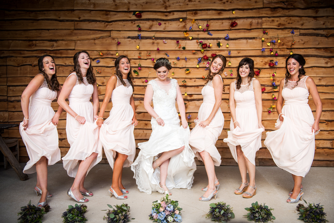 Colourful image of the bride and her bridesmaids shaking their dresses at a wedding at Tower Hill Barns.