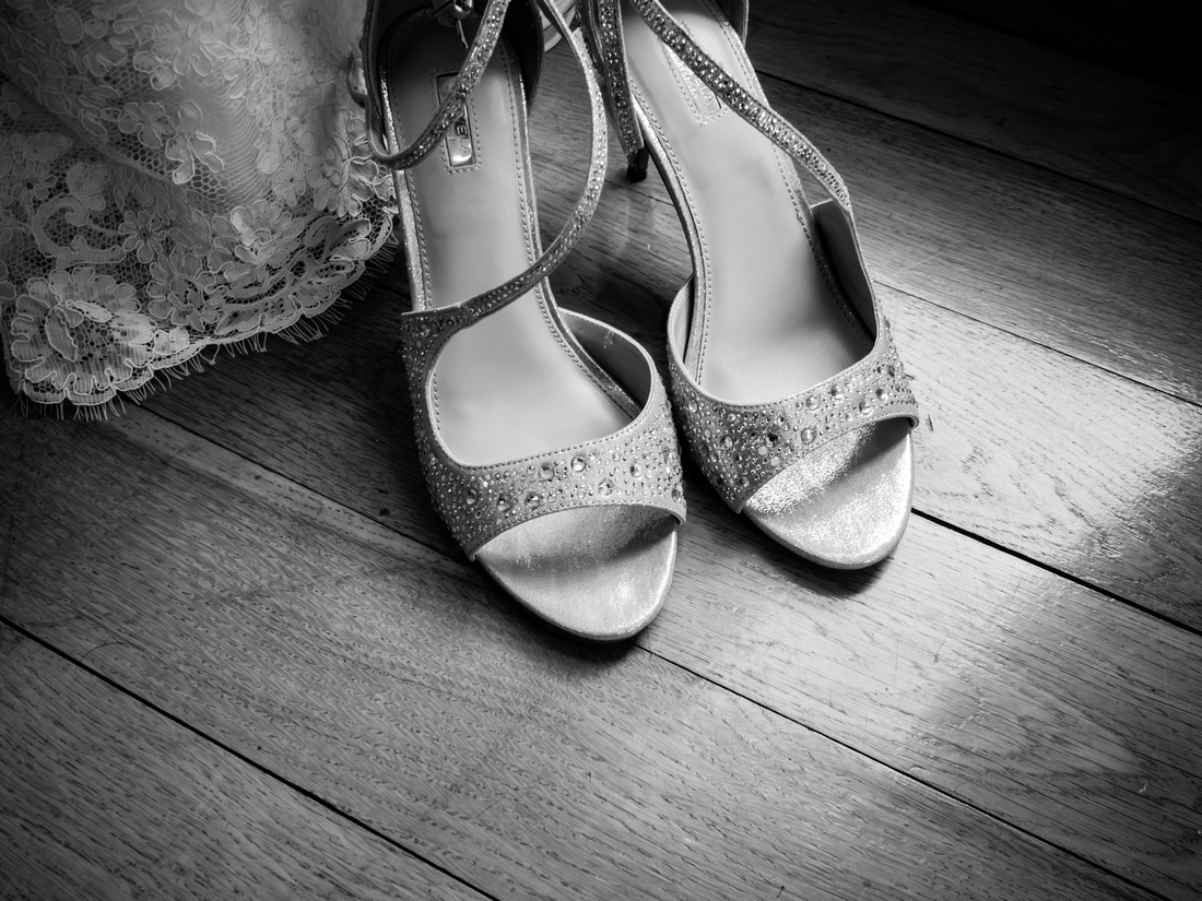 Black and white image of the bride's wedding shoes at a wedding in Portmeirion.