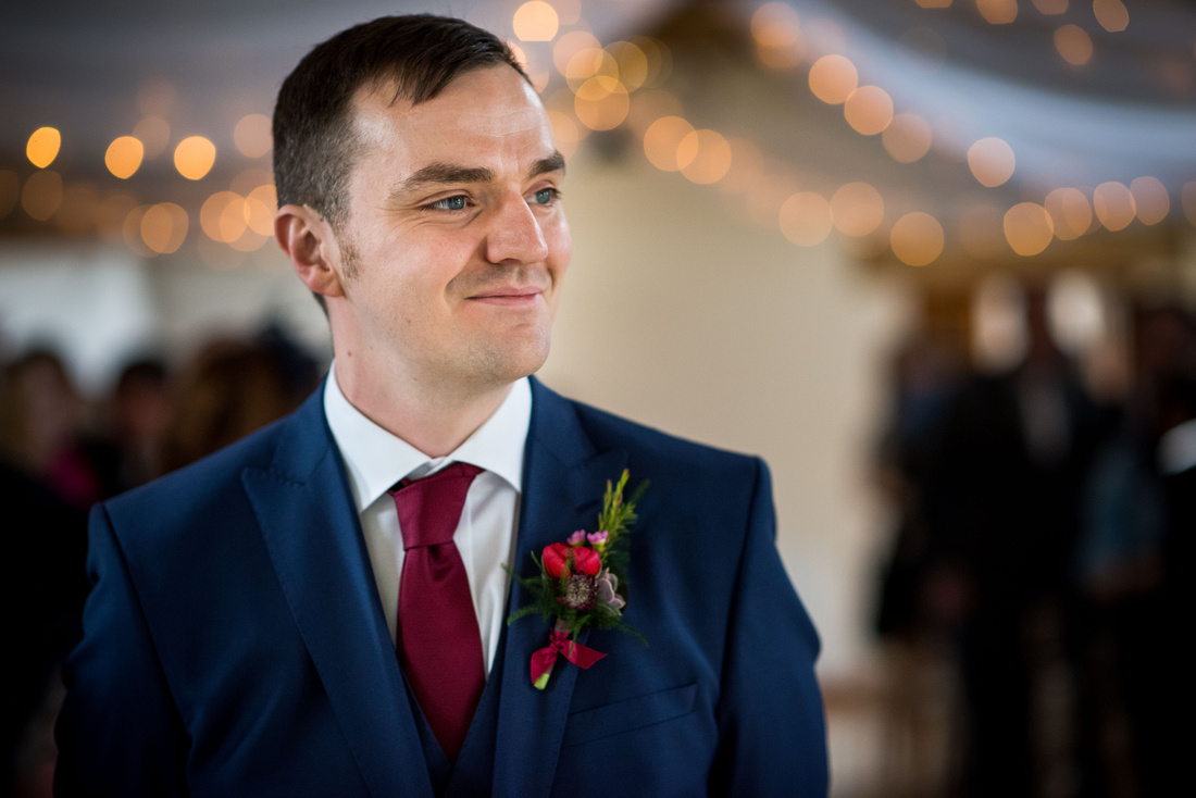 Photograph of the groom waiting for his bride to walk down the aisle at Beeston Manor.