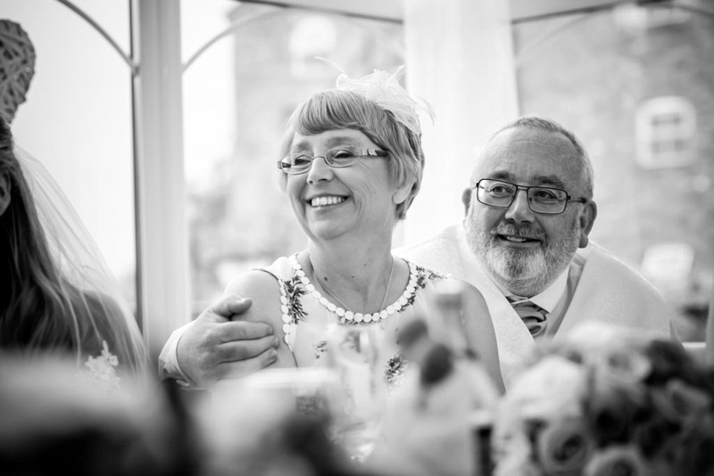 Black and white image of the bride's parents looking proud at a wedding at The Lion Quays.