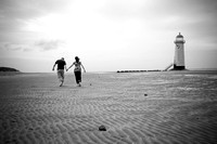 Black and white picture of a couple holding hands on their way to the lighthouse on Talacre beach
