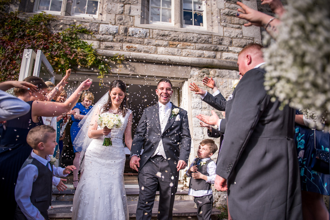 Bride and groom getting showered with confetti at their wedding at Chateau Rhianfa.