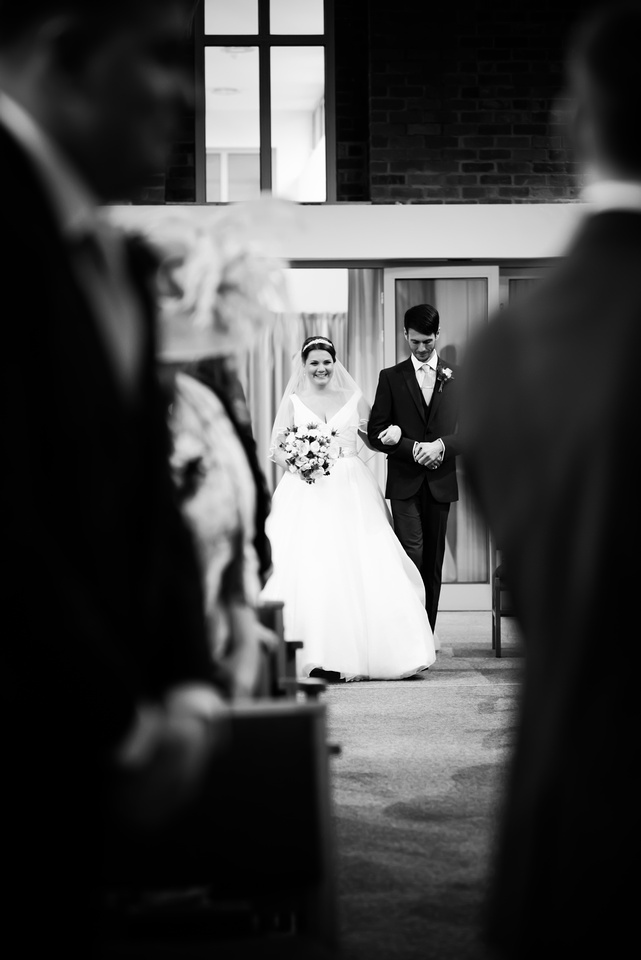 Black and white image of the bride walking down the aisle towards her groom.