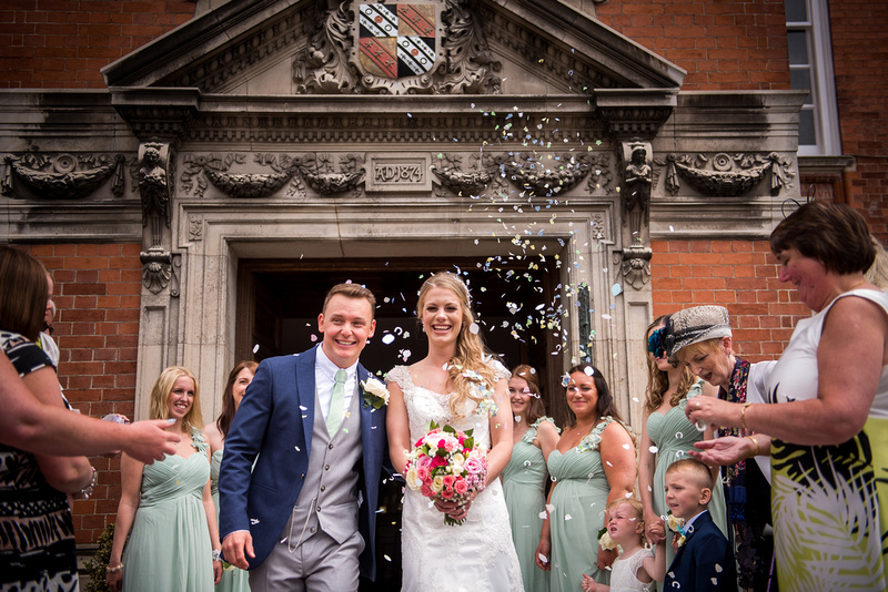 The bride and groom getting showered with confetti after their wedding ceremony at Bodrhyddan Hall.