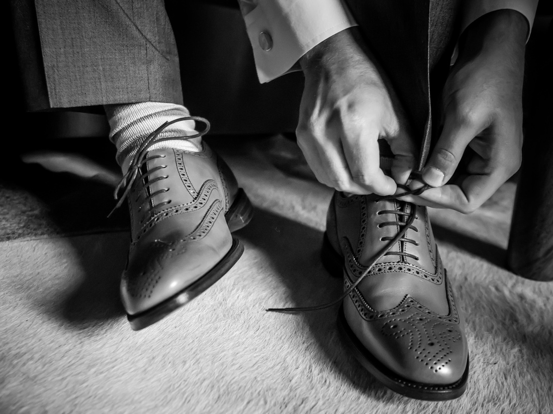 Black and white image of the groom putting on his shoes for his wedding day Pentre Mawr.