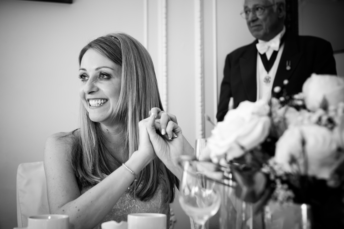 Black and white image of the bride smiling during the speeches at a wedding at Taplow House, Buckinghamshire.