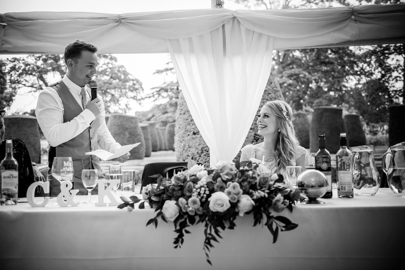 Black and white image of the groom looking at the bride during his speech at his wedding at Bodrhyddan Hall.