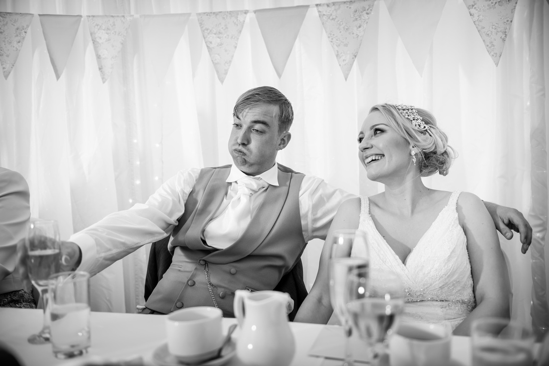 Black and white image of the bride and groom during the best man's speech at their wedding at Pentre Mawr.