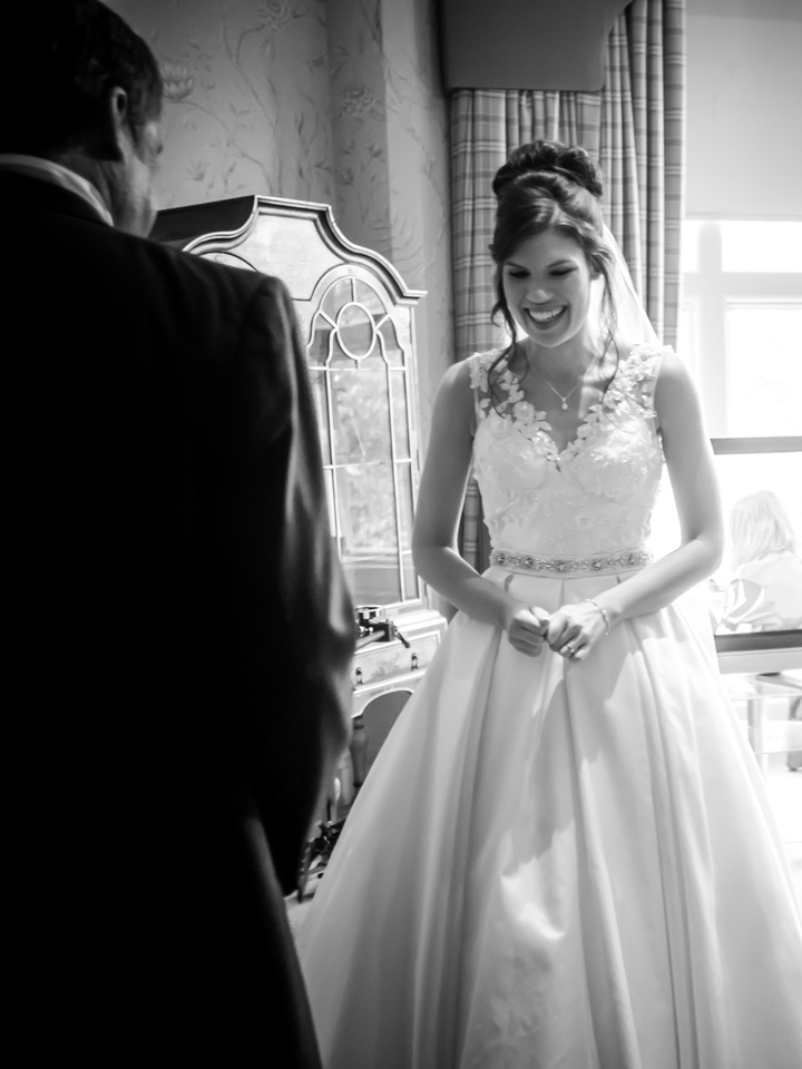 Black and white image of the bride when she sees her dad for the first time as a bride, at Ruthin Castle.