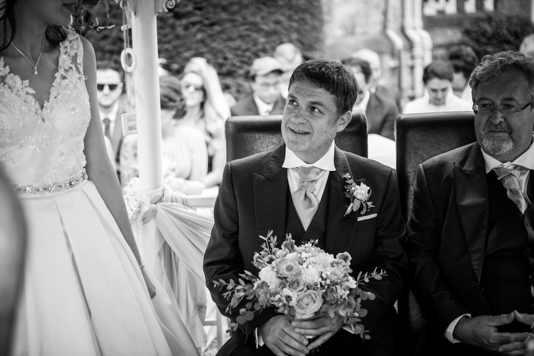 Black and white image of the father admiring his daughter during the wedding ceremony at Ruthin Castle.
