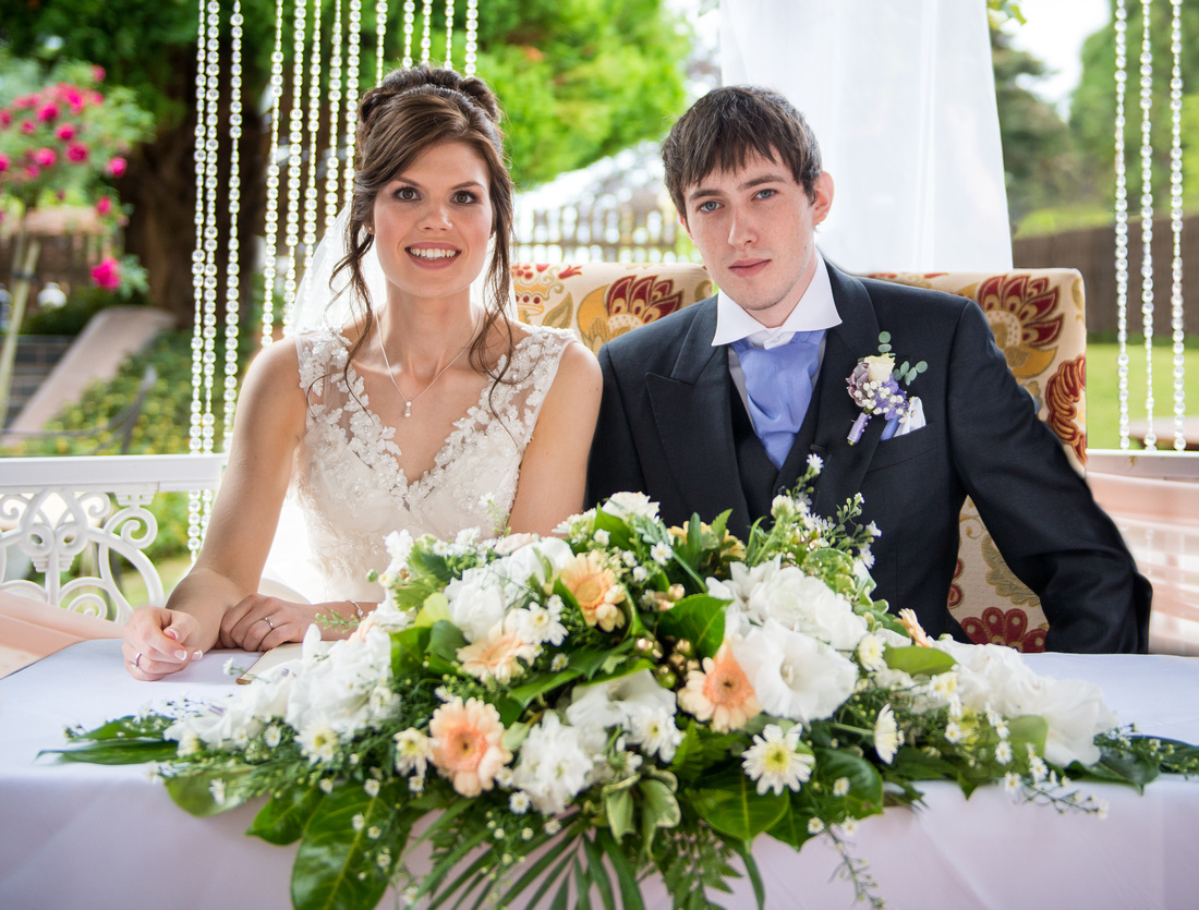 Portrait of the bride and groom after they have signed the register at their wedding in Ruthin Castle.