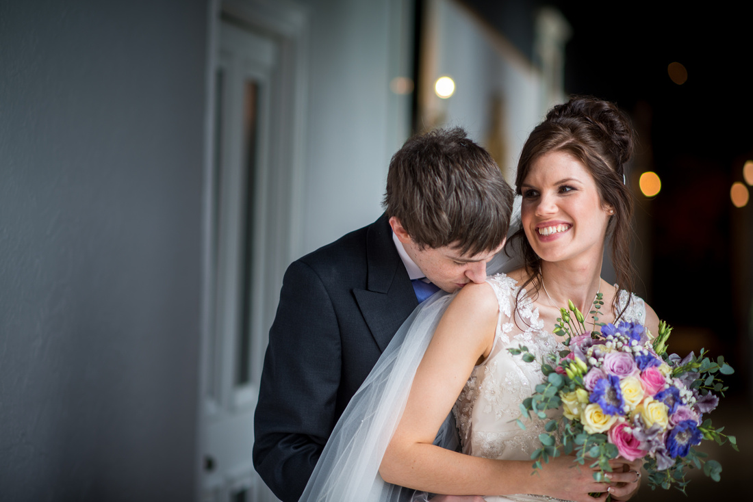Photo of groom kissing his bride's shoulder at Ruthin Castle.