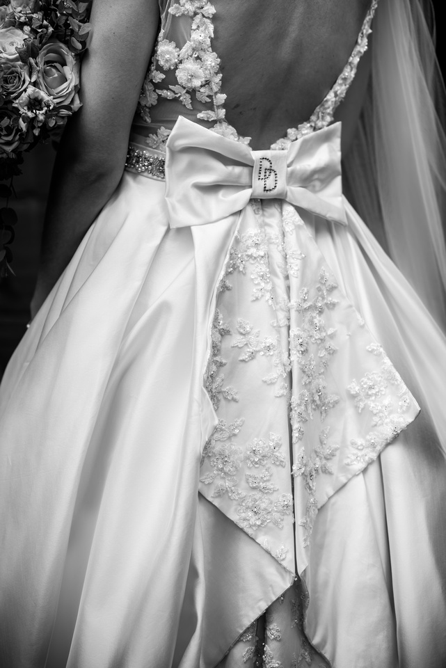 Black and white image of the back of the bride's dress, from a wedding at Ruthin Castle.