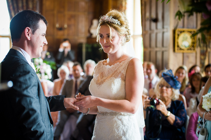 Bride and groom exchanging rings at their wedding at Chateaux Rhianfa, Anglesey. Wedding Photographer, Celynnen Photography