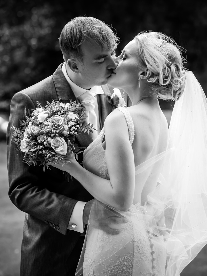 Black and white sharing a kiss on their wedding day at Pentre Mawr.
