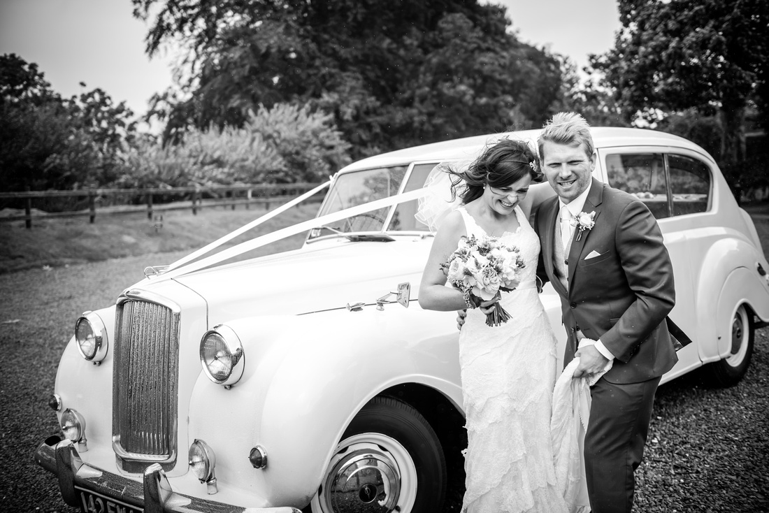Black and white image of the bride and groom arriving at a windy and rainy Plas Isaf.