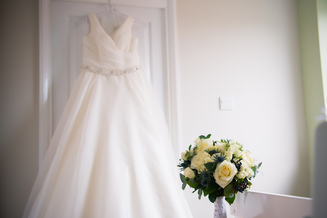Photo of the bride's wedding dress and bouquet for a wedding at Mere Brook House.