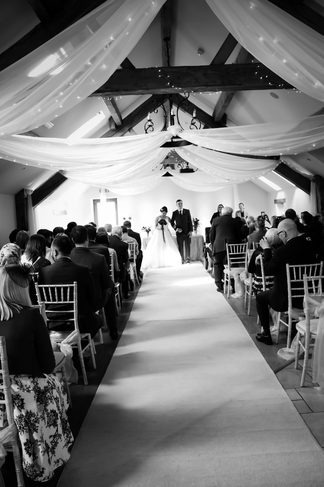 Black and white image of the bride and groom getting ready to leave the wedding ceremony as a married couple, at Beeston Manor.