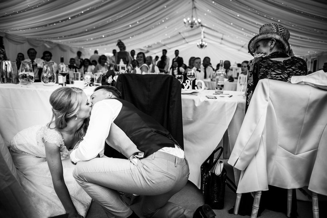 Bride and groom kissing behind the table on their wedding day at Bodrhyddan Hall by North Wales wedding photographer Celynnen Photography