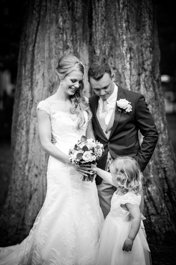 Black and white image of the flower girl stealing the bride's bouquet at Bodrhyddan Hall.