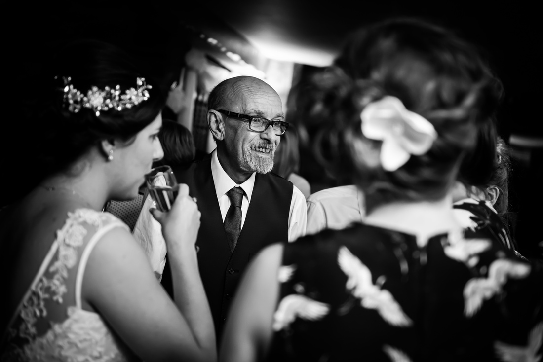 Black and white image of people enjoying themselves at a wedding at Beeston Manor.