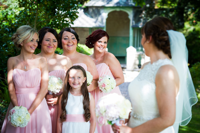 The bridesmaids smiling at the bride in the gardens during a wedding in Chateaux Rhianfa, Anglesey. Wedding Photographer, Celynnen Photography