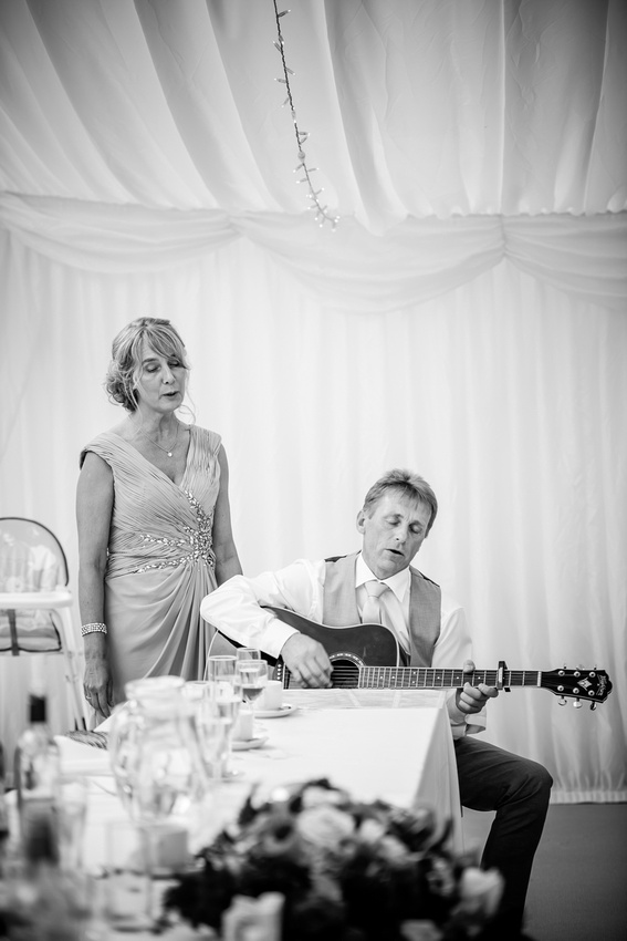 Black and white image of the parents of the bride singing at Bodrhyddan Hall.